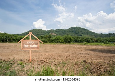 Empty dry cracked swamp reclamation soil, land plot for housing construction project with car tire print in rural area and beautiful blue sky with fresh air Land for sales landscape concept