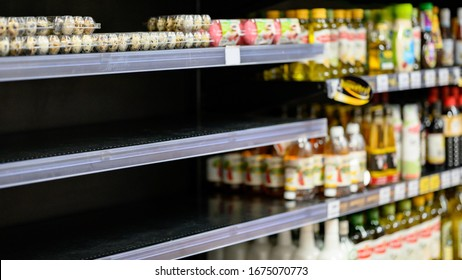 Empty egg shelves in a grocery store or supermarket. Hoarding food due to Coronavirus outbreak. Prepare food supplies for the worst case of COVID-19 pandemic. Stockpiling crisis all around the world.