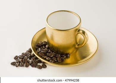 Empty Espresso gold coffee cup with beans on white