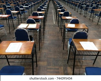 An empty exam hall with chair and desk with exam paper on desk. Phone captured