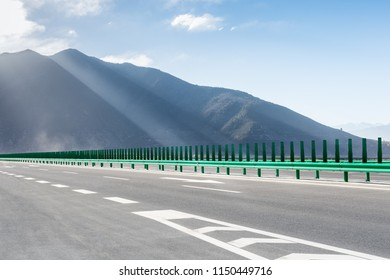 empty expressway and mountain background with dramatic light