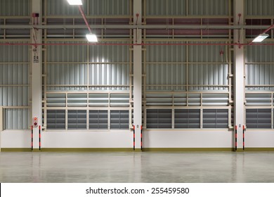 Empty factory or warehouse and concrete floor use for background, night time.