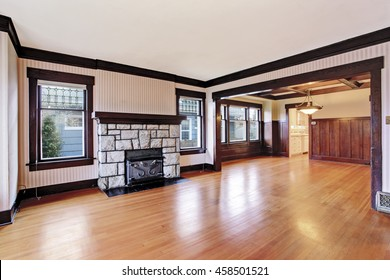 Empty Family room with white ceiling and dark brown trim, antique stone fireplace and hardwood floor. View of unfurnished room with wood paneled walls. Northwest, USA