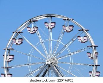 An empty ferris wheel in Maine on a blue sky day