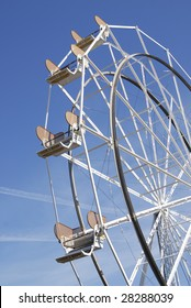 Empty Ferris Wheel on a bright sunny day with blue sky.