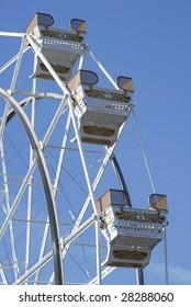 Empty ferris wheel seats with a blue sky.