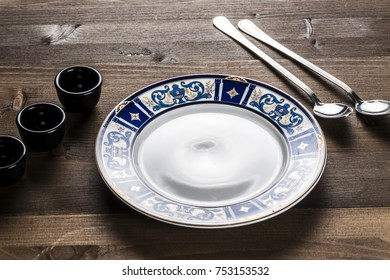 Empty figured plate, long spoons, dark wooden table