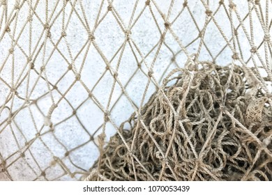 Empty fishnets on light blue shabby wall. Closeup.