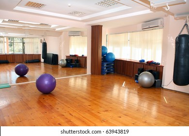 empty fitness gym with mirrors and wooden floor
