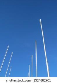 Empty flagpoles on a blue sky background
