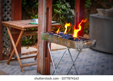 Empty flaming charcoal grill with open fire, ready for product placement.Summer Weekend BBQ Scene On The Patio Backyard,grill and table on porch deck.  Concept of summer grilling, barbecue and party.