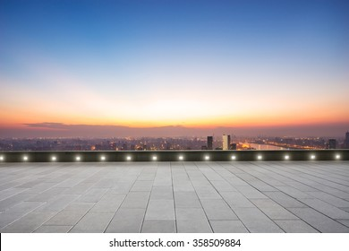 empty floor with backdrop on modern cityscape at sunrise time