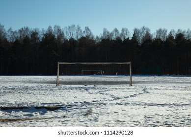 Empty football field covered in snow with a treeline behind