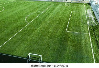 Empty football or soccer field with artificial grass or synthetic grass. Goal post and white lines penalty box.