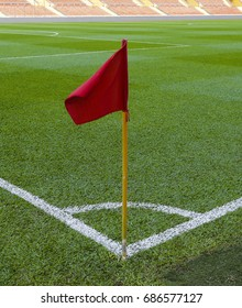 Empty football soccer field with white marks, green grass texture and red corner flag.