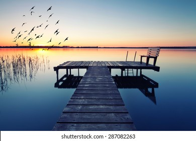 empty footbridge with a bench on a lake near Berlin at sunrise