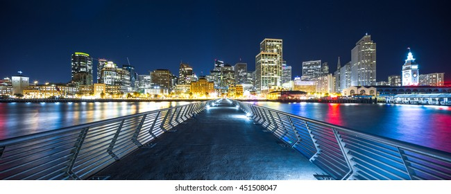 empty footpath over water to modern office buildings in san francisco at night