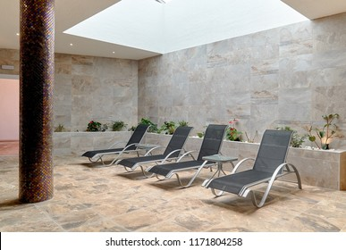 Empty four gray lounge chairs inside of tiled room. Nobody in spa room. Deck chair for clients relaxation after spa procedures, bath house and swimming in pool. Modern and comfortable interior design