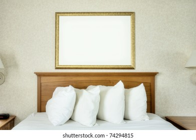 An empty frame hangs on the wall over a bed.