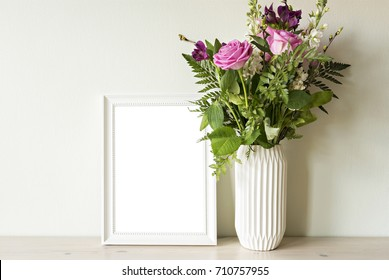 Empty frame mockup with flower bouquet in vase