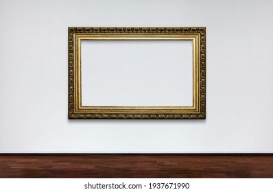 Empty frame on white wall in Museum. place for pictures. Antique Framework. Vintage picture frame on white wall.