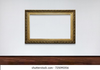 Empty frame on white wall in Museum. place for pictures. Antique Framework. Vintage picture frame on white wall