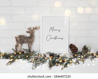 empty frame, reindeer and Christmas garland in white wall