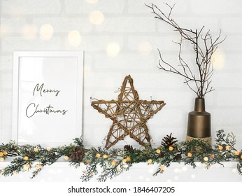 empty frame, star and Christmas garland in white wall