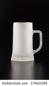 An empty and frozen glass tankard over black background