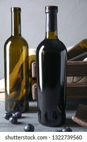 Empty and full bottles of wine  with grapes on wooden table