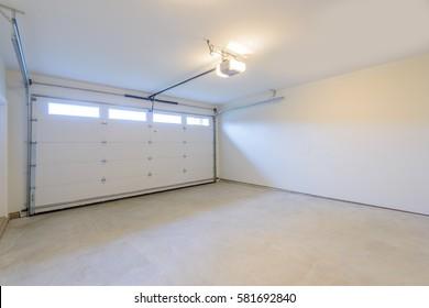 Un garaje vacío con puerta y ventanas.