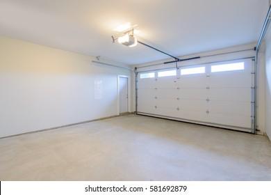 An empty garage with door and windows.