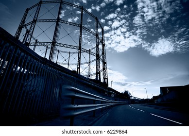 Empty gasometer and street