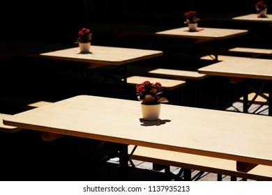 empty german biergarten or beer garden, wooden outdoor tables and benches