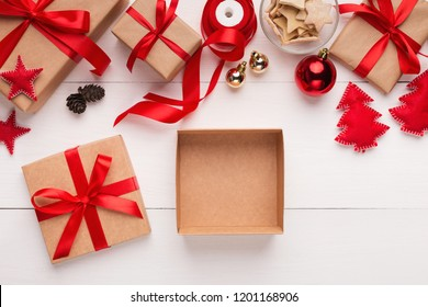 Empty gift box for Christmas or New Year holiday present, top view on white table with xmas decorations, copy space