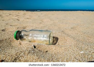Empty glass bottle dumped on the beach