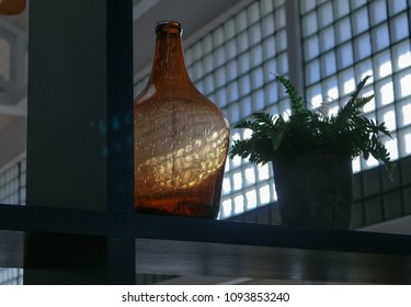 Empty glass bottle on a shelf.