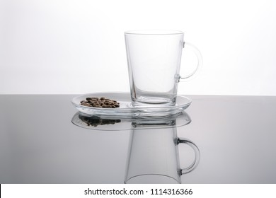 Empty glass coffee cup and roasted coffee beans. White background, dark surface.