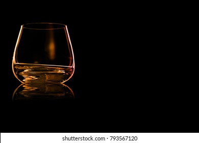 Empty glass of cognac with fire reflection isolated on a black background. Place for your text.