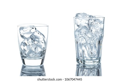 Empty glass with ice cubes on white background