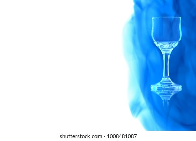 Empty glass of liqueur or vodka on white background enveloped in puff of blue smoke.