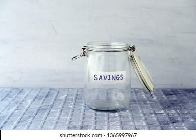 Empty glass money jar with savings label, financial concept.