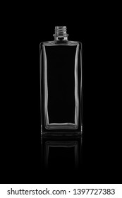 Empty glass perfume bottle isolated on a black background with reflection