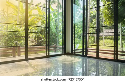 Empty glass room corner with morning sunlight, balcony and trees garden view, cozy and restful room interior concept