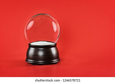 Empty glass snow globe with wooden base against a red background. Free copy space for text included.
