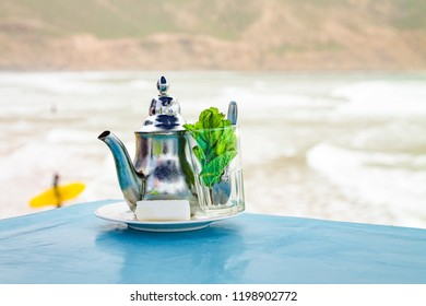 An empty glass for a traditional Berber mint tea with an iron kettle, a sprig of mint and a large piece of sugar. A traditional Berber drink is mint tea against the backdrop of the Atlantic Ocean and