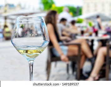 Empty glass from wine and blurred silhouettes of people in Mediterranean cafe outdoors