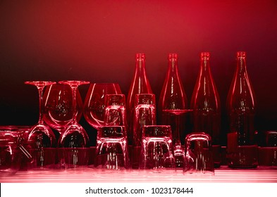 Empty glasses and bottles under hazy red light on bright LED light counter bar and illuminated red light on dark wall background