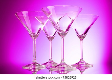 empty glasses of martini on purple background