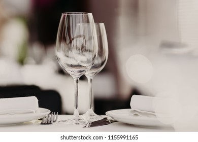 Empty glasses stand near plates and forks on banquet table decorated with white tablewear. Festively served table against blurred background in restaurant